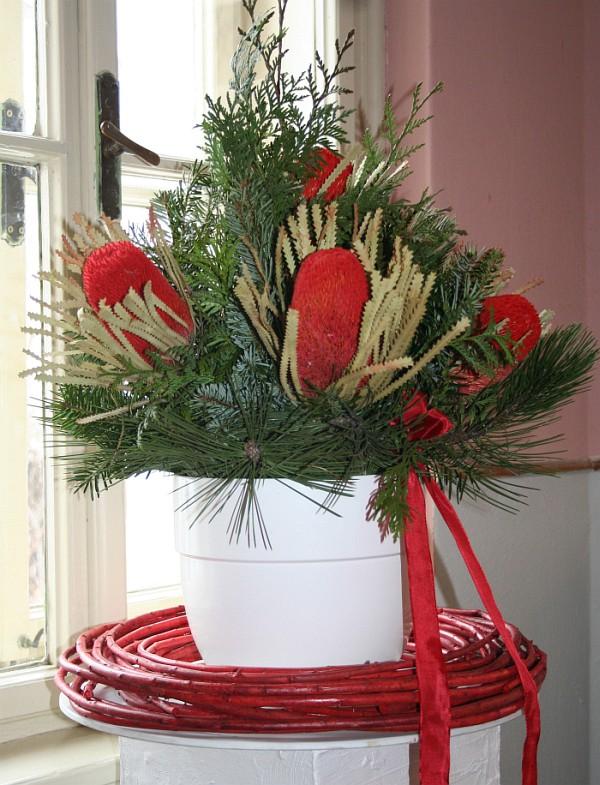 Spojení exotiky s tújí a chvojím. Červený proutěný věnec zimní aranž barevně umocňuje.