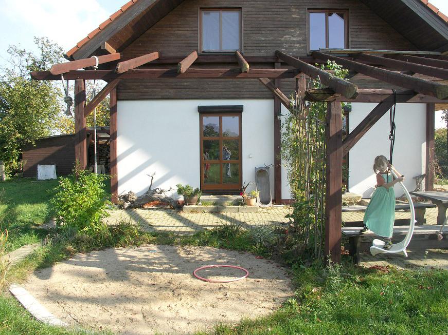 Masivní dřevěná pergola nad obytnou terasou u venkovského domku